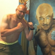 A studly man standing next to a painting of another studly man, both with dukes up.